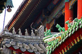 Qilin and dragon figurines adorn the roof of a lama temple in Be — Stock Photo