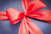 Classic red ribbon on blue background — Stock Photo