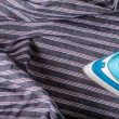 Ironing man shirt on stripes — Stock Photo