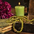 Old book, flower, candle and open jewelry box with green necklace still life, renaissance concept with dark grunge light — Foto Stock