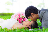 Asian groom and bride embrace — Stock Photo