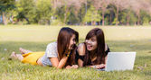 Young pretty woman with laptop lying in a park — Stock Photo