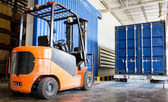 Forklift in warehouse with container — Stock Photo