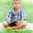 Boy holding tablet PC in garden — 图库照片