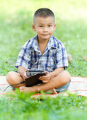 Boy holding tablet PC in garden — Stock Photo