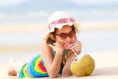 Young woman in swimsuit with coconut cocktail on the beach — Stock Photo