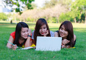 Young students group with computer studying in spring outdoors — Foto de Stock
