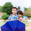 A smiling boy and a little girl with umbrella in the park — Stock Photo