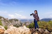 Nature photographer with digital camera on top of the mountain — Stock Photo