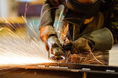 Electric wheel grinding on steel structure in factory — Stock Photo