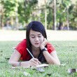Beautiful young brunette woman writing in her diary — Photo