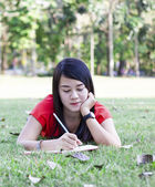 Beautiful young brunette woman writing in her diary — Stockfoto