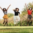 Foto Stock: Excited group of friends jumping at park