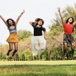 Excited group of friends jumping at the park — Stock Photo #35698535