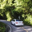 Hilly asphalt road with white car — Stock Photo