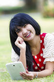 Asia woman using tablet outdoor laying on grass — Stock Photo