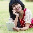 Stock Photo: Young womusing her tablet pc