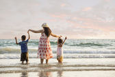 Happy family standing on the beach on the dawn time — Stock Photo