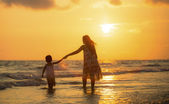 Mother with her daughter on the beach — Stock Photo