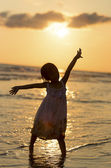 Happy girl standing on the beach on the dawn time — Stock Photo