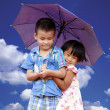 Smiling boy and little girl with umbrella — Stock Photo