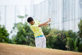 Male golfer hitting golf ball out of a sand trap — Stock Photo