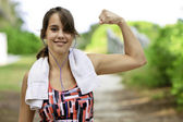Teenage girl flexing her muscle — Stockfoto