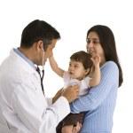 Doctor listening to little girls heartbeat — Stock Photo