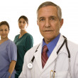 Senior doctor with two nurses — Stockfoto
