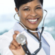 Smiling female doctor with out of focus stethoscope — Stock Photo