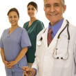 Senior male doctor with two nurses — Stock Photo