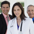 Smiling doctor with two businessmen — Stock Photo