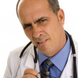 Stock Photo: Puzzled doctor holding glasses