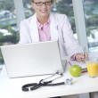 Female doctor behind desk — Stock Photo