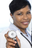 Out of focus female doctor holding stethoscope — Stock Photo