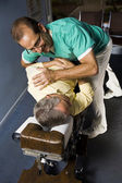 Chiropractor adjusting senior man — Stock Photo
