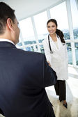 Businessman and doctor shaking hands — Stock Photo