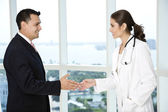 Businessman and female doctor shaking hands — Stock Photo