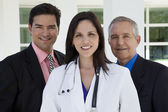 Happy doctor with two businessmen — Stock Photo