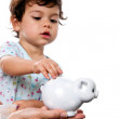 Toddler putting coin in piggy bank — Stock Photo