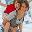 Stock Photo: Sister with brother on piggy back