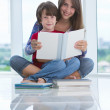 Teenage girl reads to boy — Stock Photo