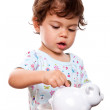 Toddler putting money in piggy bank — Stock Photo