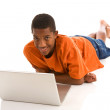 Stock Photo: Teenage boy laying with laptop