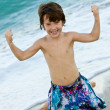 Boy flexing muscles — Stockfoto