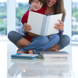 Teenage sister reading with brother — Stock Photo