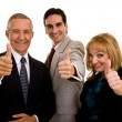 Three businesspeople giving a thumbs up — Foto Stock