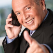 Businessman using cellphone and thumbs up — Stock Photo