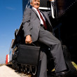 Stock Photo: Senior businessmholding on to train