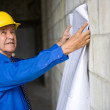 Senior man holding blueprints and wearing hardhat — Stock Photo